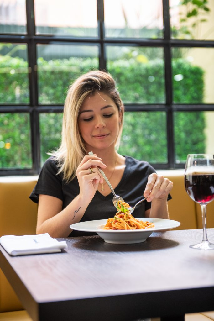 Woman eating past with a glass of red wine